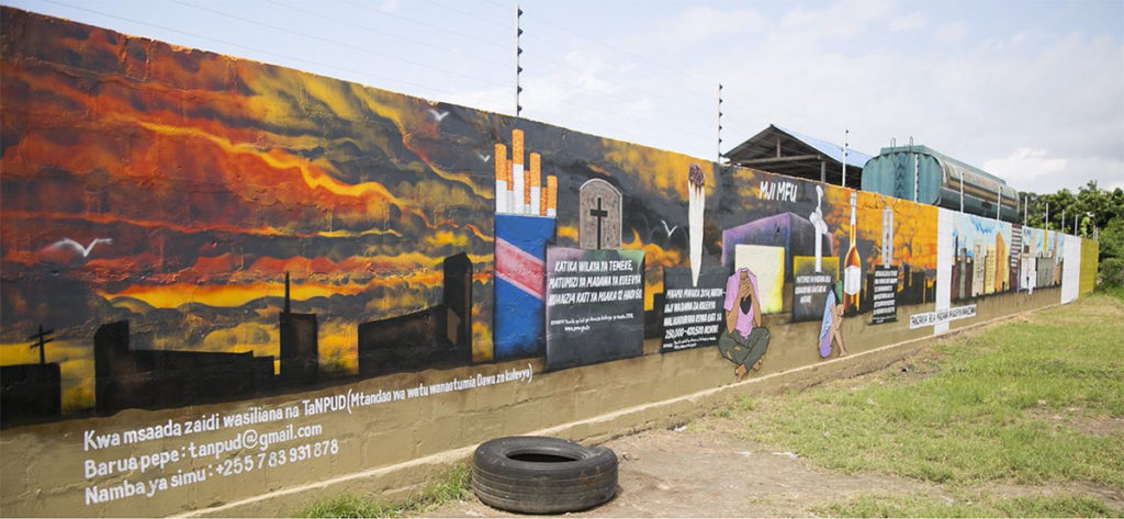 A wall mural in Temeke District contrasts a drug-riddle city in despair (left side) against a drug-free Tanzania. Text embedded in the mural shows data about the extent of drug abuse in the area. Photo Credit: TBI production team.